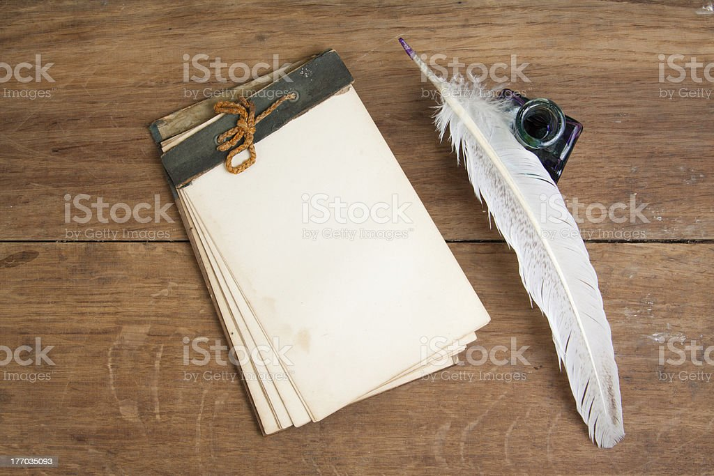 Vintage notebook, quill and inkwell on wood background royalty-free stock photo