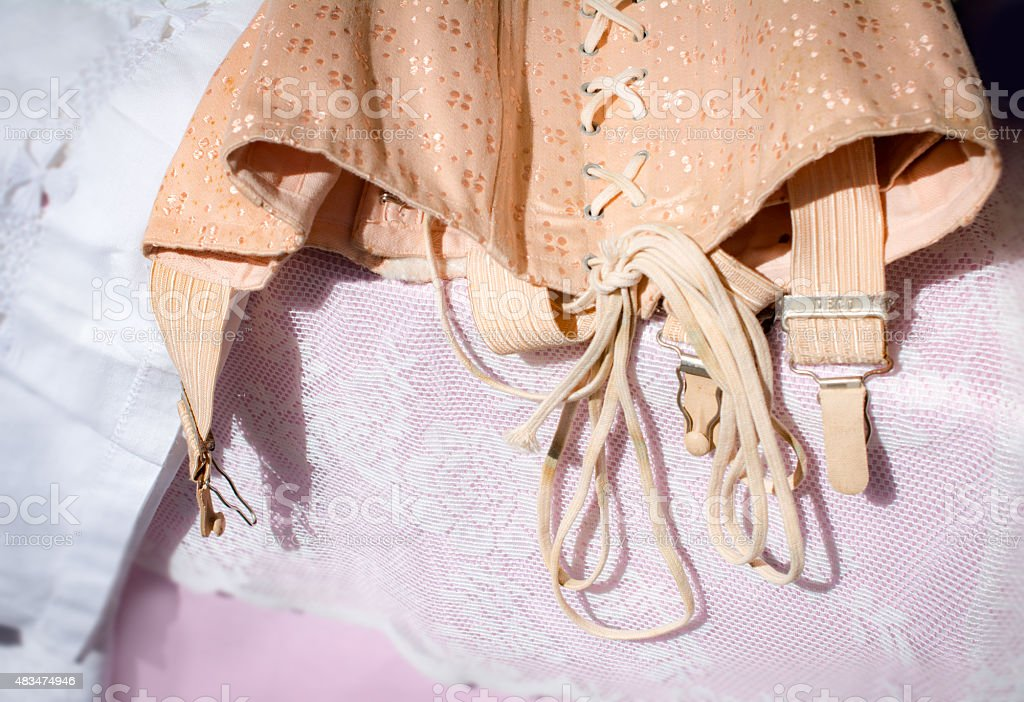 Vintage nude color corset  on a pink lace table stock photo
