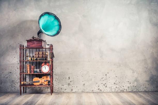 Vintage-Objektsammlung: Antikestregender Grammophon-Phonograph mit Aquamarin-Horn, alte Bücher, Wecker, Fotokamera, Kerzenständer, Fernglas, Geige, Schlüssel im Regal. Retro-Stil gefilterte Fotografie – Foto