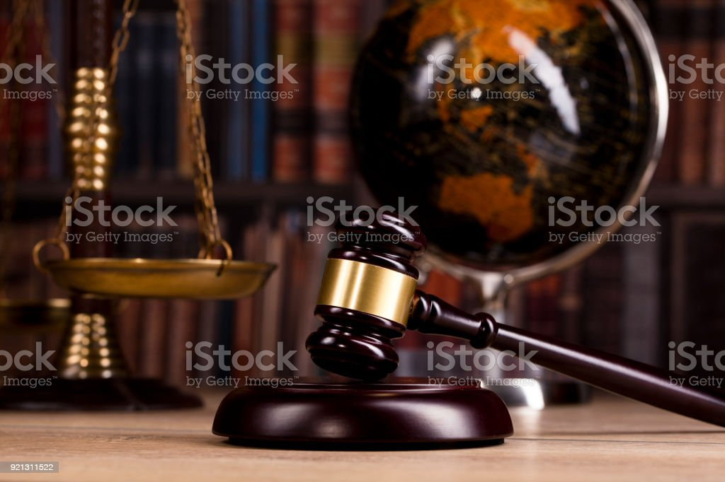 Vintage office room in a law firm with the legal hammer and an old globe on the table with law books in the background stock photo