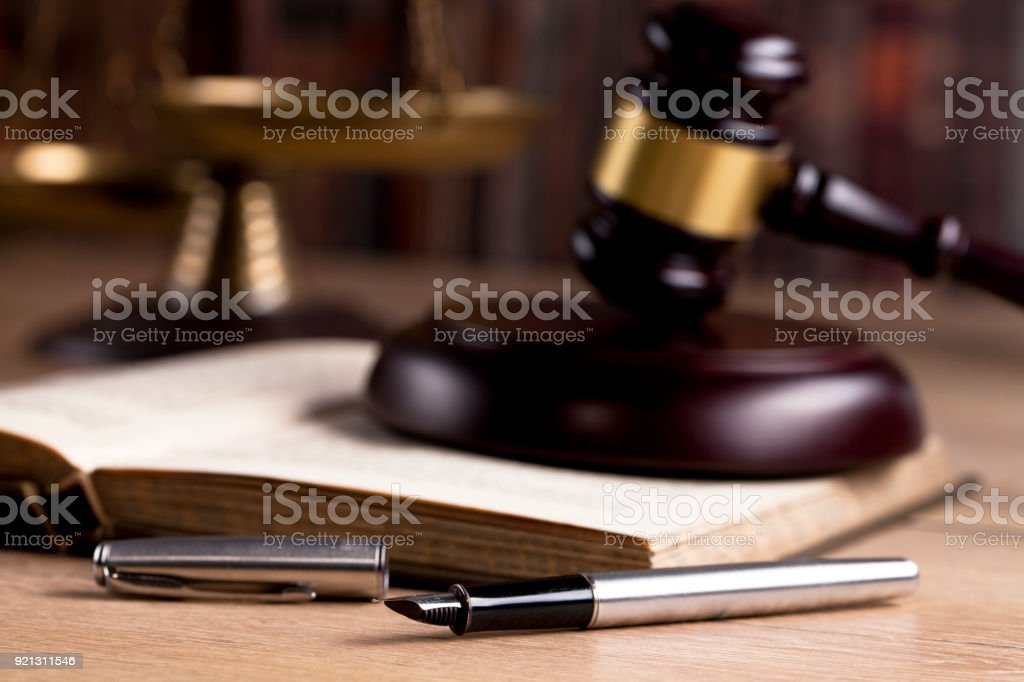 Vintage office room in a law firm with the legal hammer and an old fountain pen on the table with law books in the background. stock photo