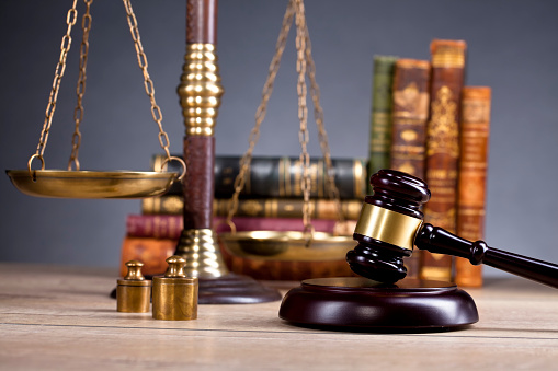 Vintage Office Room In A Law Firm With The Legal Hammer And The Scales Of Justice On The Table With Law Books In The Background Stock Photo - Download Image Now - iStock