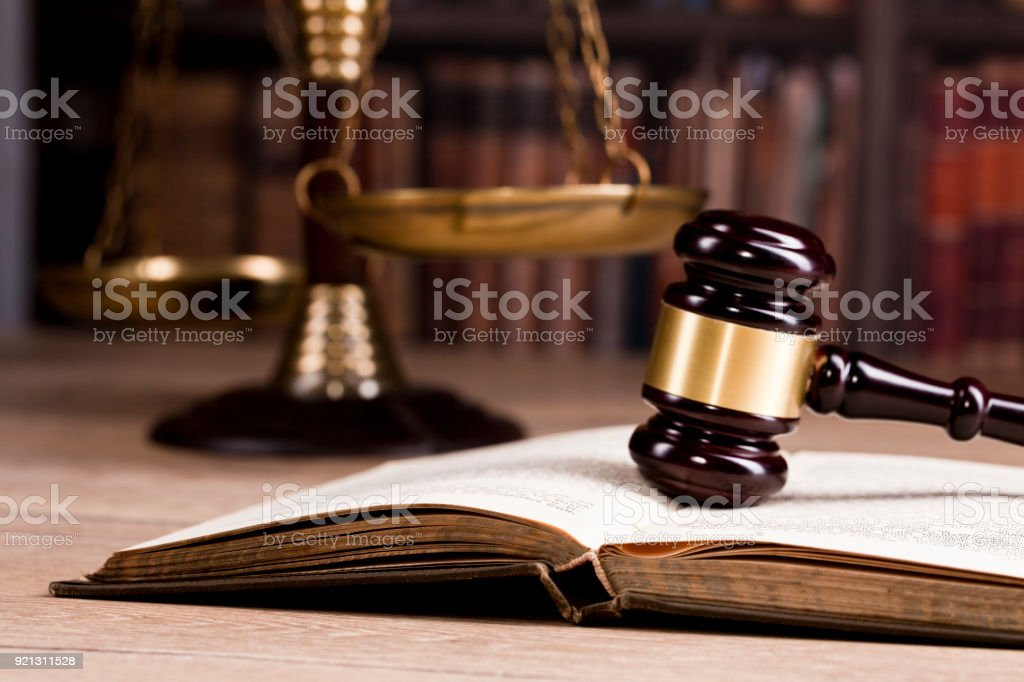 Vintage office room in a law firm with the legal hammer on an open book and the scale of justice on the table with law books in the background. stock photo