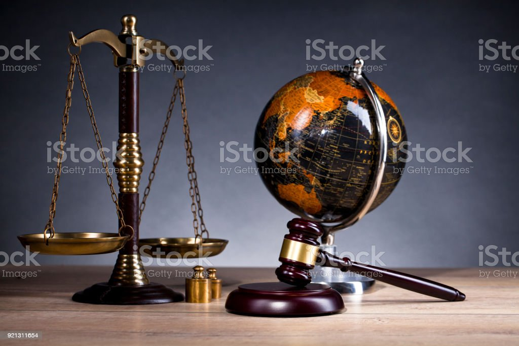 Vintage office room in a law firm with the legal hammer, scales of justice and an old globe on the table. stock photo
