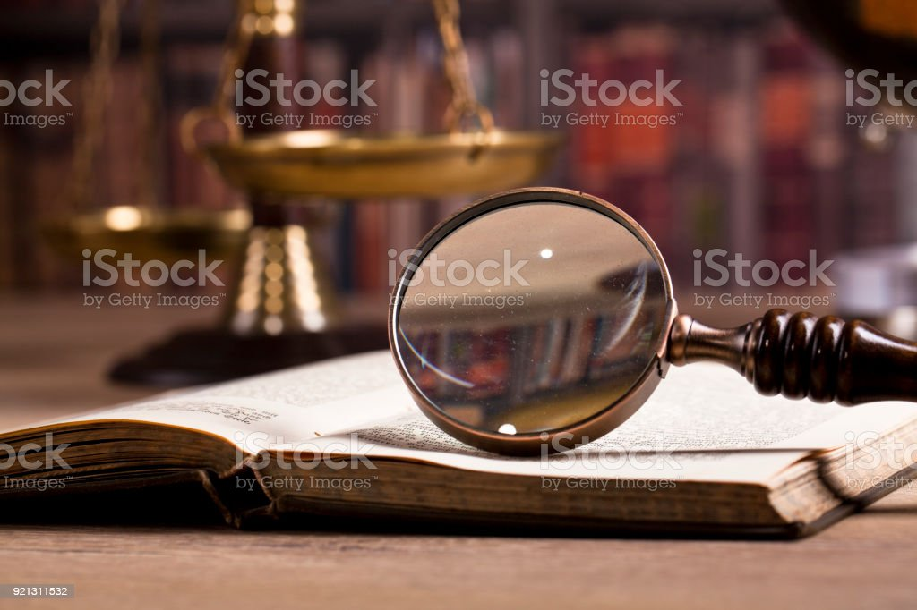 Vintage office room in a law firm with the magnifying glass and the scale of justice on the table with law books in the background. stock photo