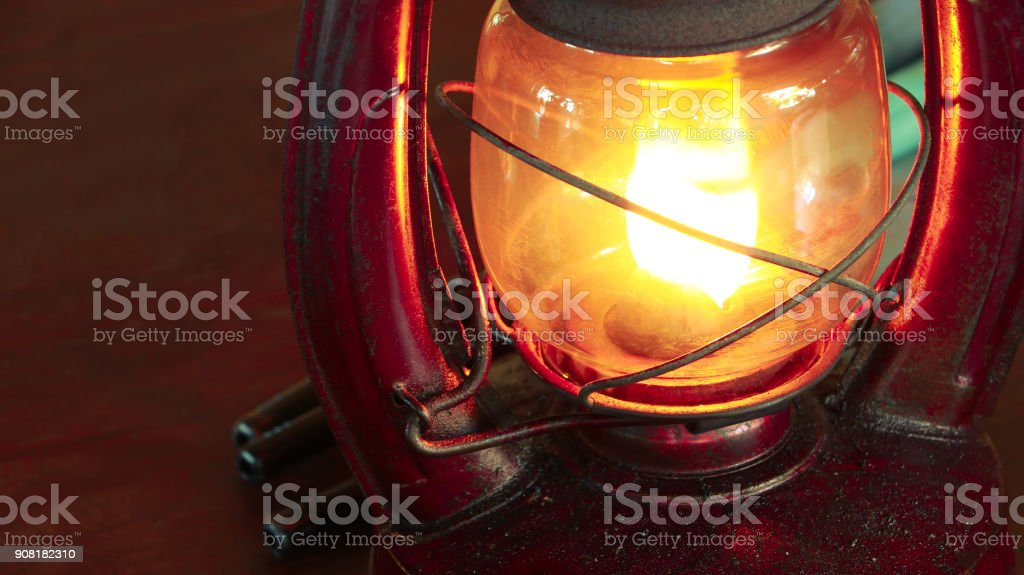 Vintage oil lamp antique stands on the table in the dark. Oil filled lantern in dark room. stock photo