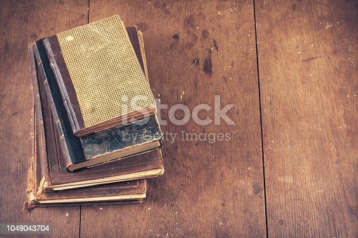 Vintage old books on grunge wooden table background. Retro instagram style filtered photo