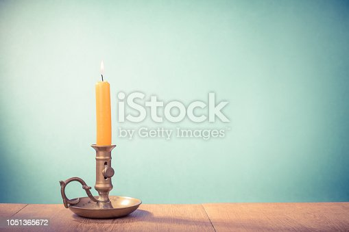 Vintage old bronze candlestick with burning candle. Retro style filtered photo