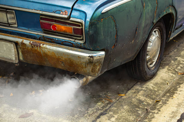 Vintage old car emits pollutant out of the exhaust stock photo