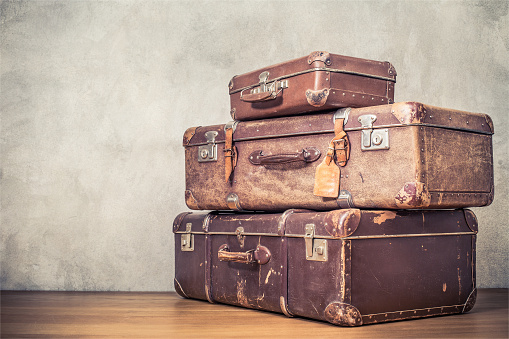 istock Vintage old classic travel leather suitcases circa 1940s. Travel luggage concept. Retro instagram style filtered photo 1055064410