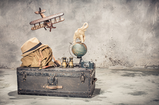 Vintage old classic travel trunk luggage, flying wooden toy plane, elephant on aged globe, tourist backpack, hat, binoculars, film camera, magnifier. Travel by air concept. Retro style filtered photo
