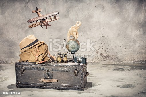 istock Vintage old classic travel trunk luggage, flying wooden toy plane, elephant on aged globe, tourist backpack, hat, binoculars, film camera, magnifier. Travel by air concept. Retro style filtered photo 1063668064