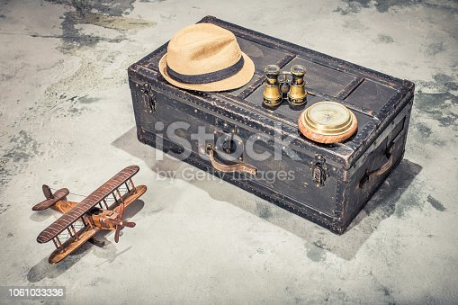 istock Vintage old classic travel trunk luggage with leather handles circa early 1900s, wooden toy airplane, compass, binoculars, men's hat. Travel by air concept. Retro style filtered photo 1061033336