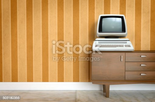 181053292istockphoto Vintage old computer on sixties, seventies wallpaper and furniture 503180355