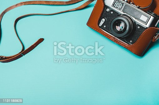 istock Vintage old photo camera on a blue background. Retro concept 1131185925