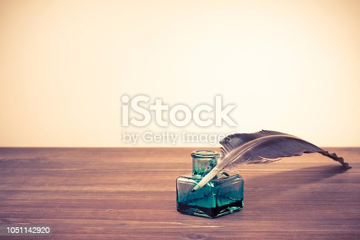 istock Vintage old quill pen with inkwell on wooden table. Retro instagram style filtered photo 1051142920