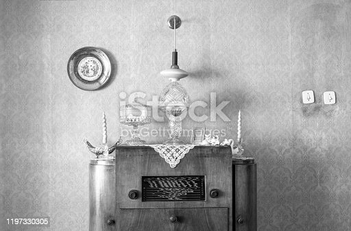 181053292 istock photo Vintage old radio on sixties, seventies wallpaper and furniture, antique, black and white 1197330305