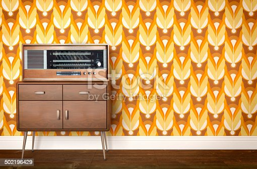 istock Vintage old radio on sixties, seventies wallpaper and furniture 502196429
