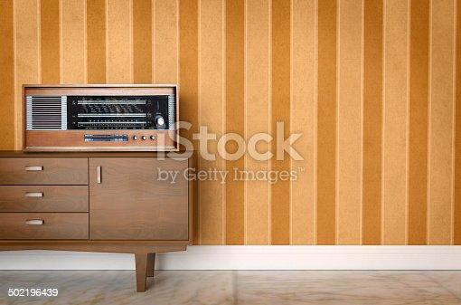 181053292istockphoto Vintage old radio on sixties, seventies wallpaper and furniture 502196439