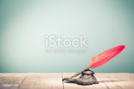 istock Vintage old red quill pen and inkwell on wooden table. Retro style filtered photo 1055671124