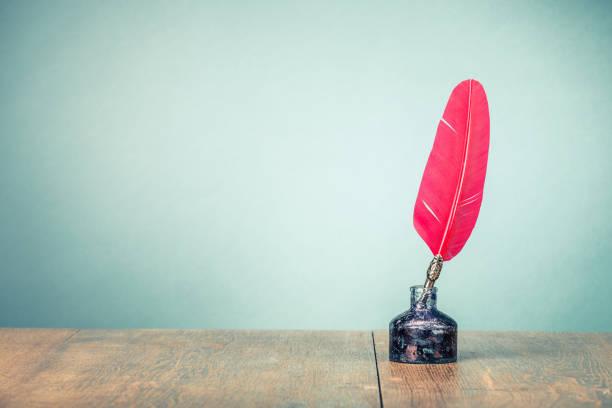 Vintage alte rote Schreibfeder mit Tintenfass auf Holztisch vorderen gradient Minze grüne Wand Hintergrund. Retro-Stil gefilterten Foto – Foto