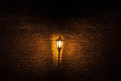 Vintage old street lantern lit with an orange light in front of a brick wall during a gloomy dark night.