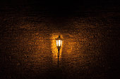 Picture of a street lamp in a street, at night, with a brick wall in background, projecting a yellow orange gloomy light.