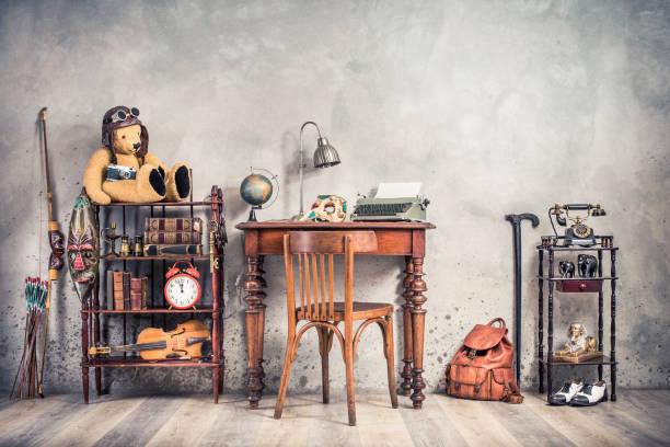 Vintage alte Schreibmaschine, Lampe, Karnevalsmaske, Globus auf antikem Tisch, Stuhl, Teddybär mit Fotokamera, Retro-Uhr, Bücher, Geige, Schlüssel im Regal, Telefon, Souvenirs, Schuhe, Stock, Rucksack, Bogen – Foto