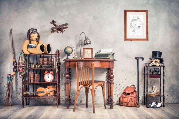 Vintage alte Schreibmaschine, Lampe, Rahmen, Zeigefinger auf antikem Tisch, Stuhl, Teddy Bär mit Fotokamera, Retro-Uhr, Bücher, Geige, Schlüssel auf dem Regal, Flugzeug, Maske, Zylindermütze, Schuhe, Stock, Rucksack, Bogen – Foto