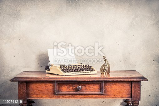 istock Vintage old typewriter with sheet of paper blank and golden forefinger on wooden table front loft concrete wall background with shadows. Retro style filtered photo 1150741219