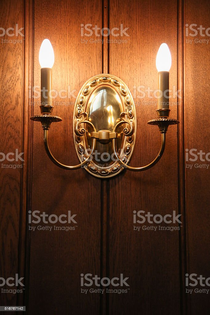 Vintage old wall candle lamp illuminates a dark room. stock photo