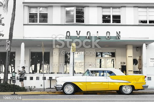25 December 2019 - South Beach Miami, USA. Classic 1955 Oldsmobile Super 88 convertible in yellow parked near Avalon Art Deco hotel.