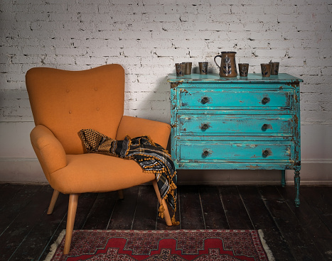 Vintage orange armchair, blue cabinet and ornate scarf