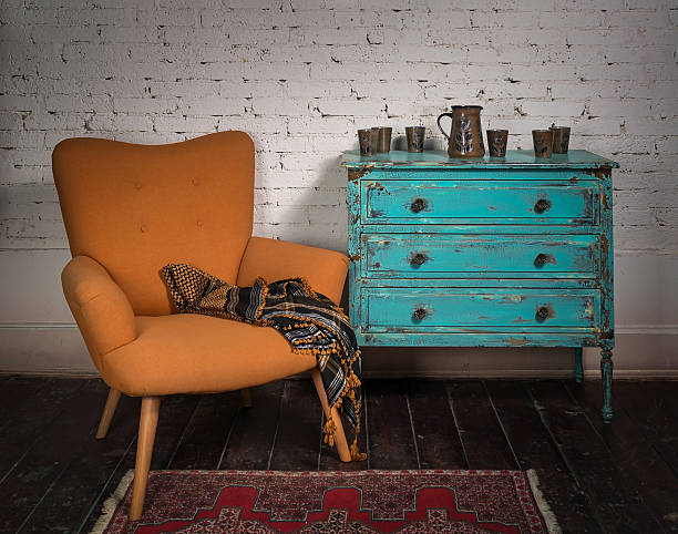 vintage orange armchair, blue cabinet and ornate scarf - retro decor stock photos and pictures