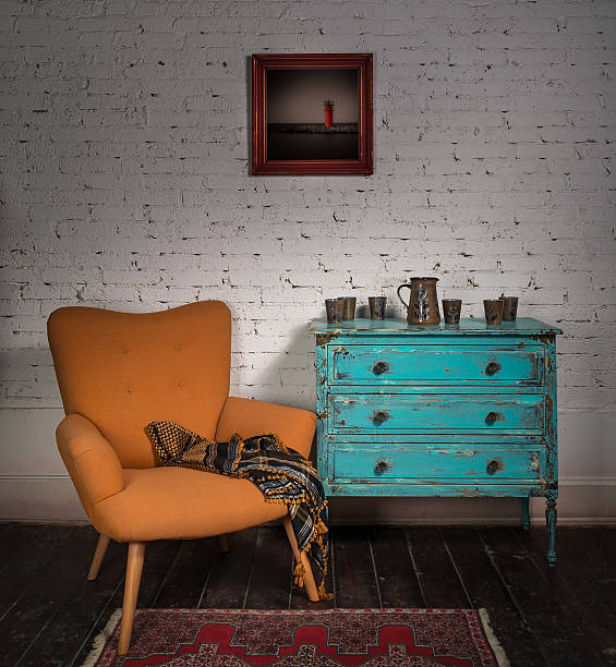 Vintage orange armchair, blue cabinet, hanged painting and ornate scarf stock photo