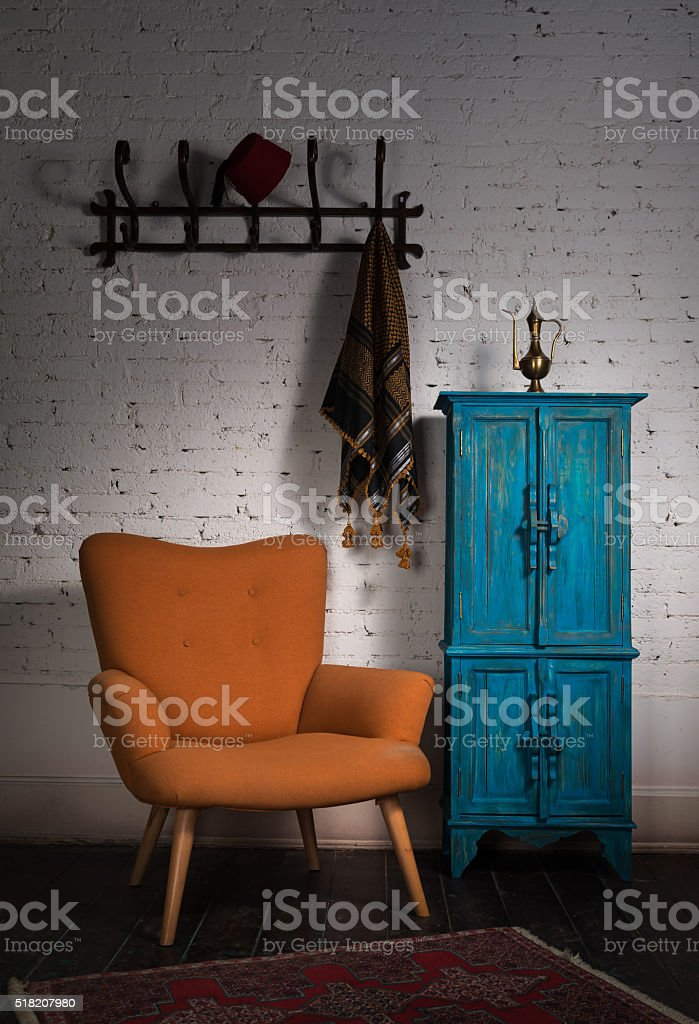 Vintage orange armchair, blue cupboard, wall hanger and black scarf stock photo