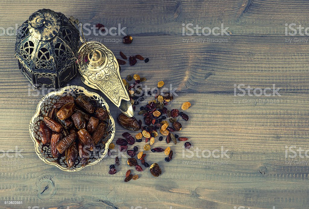 Vintage oriental latern, raisins and dates on wooden background stock photo