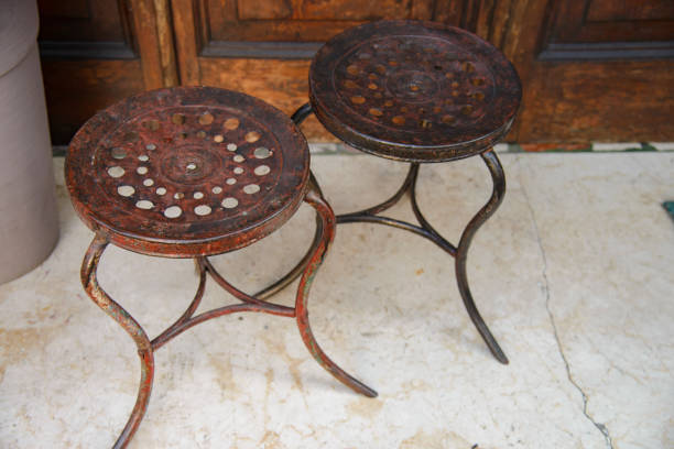 Vintage pair of old wrought iron stools. stock photo