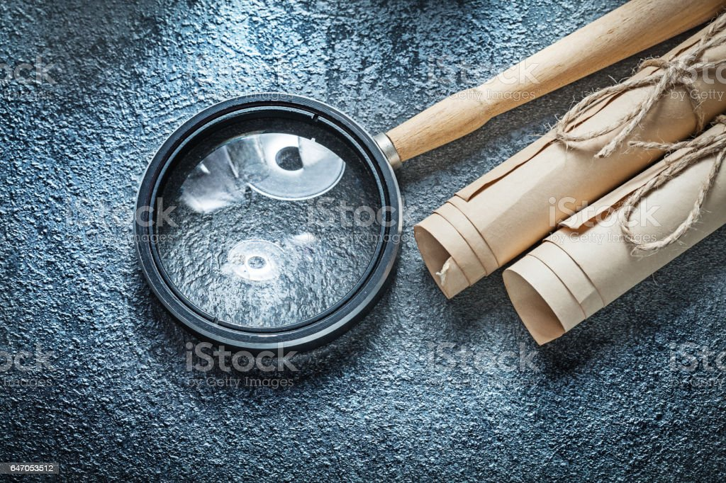 Vintage paper scrolls magnifying glass on black background stock photo