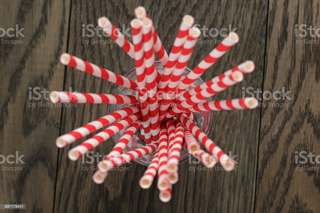 vintage paper straws in glass on wood table stock photo