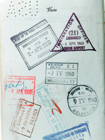 A close up view of vintage passport stamps from the 1960's