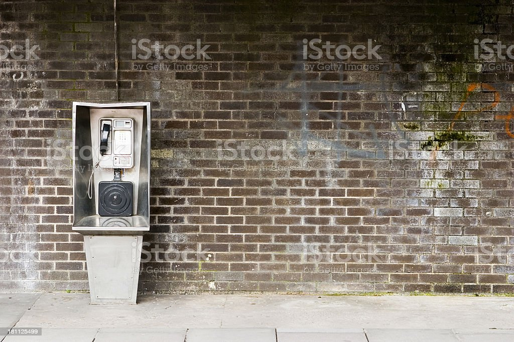 A vintage pay phone against a brick wall stock photo