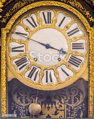 671883446 istock photo Vintage pendulum clock with gilded pattern 518558104
