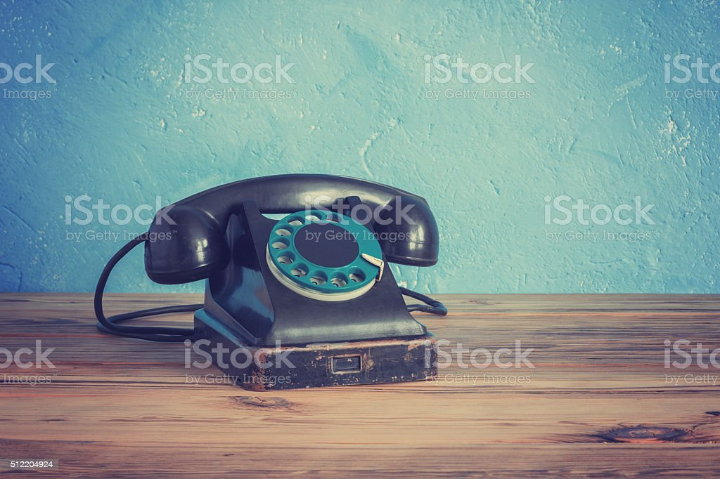 Vintage phone on a wooden table stock photo