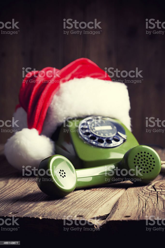 vintage phone with Santa's hat on wooden background stock photo