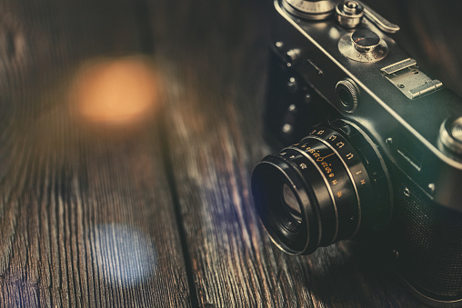 Vintage photo camera on old wooden table. Stock photo