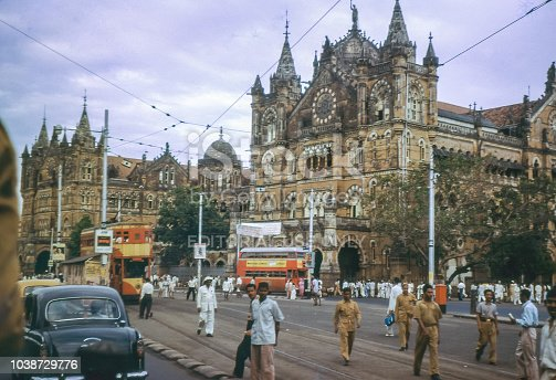 BOMBAY, INDIA - CIRCA 1962: Vintage photo of busy street in front of Victoria Terminus railway building in Bombay, now know as Chhatrapati Shivaji Maharaj Terminus, Mumbai, India. From a 35mm slide.
