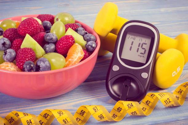 Vintage-Foto, Obstsalat, Glucometer mit Ergebnis von Zuckerstand, Zentimeter und Hanteln, Diabetes, gesunder Lebensstil und Ernährungskonzept – Foto