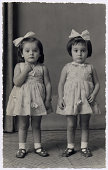 Hi-res scan of an italian photograph dated 1957. Two little twin sisters are looking at camera with identical frocks, hair bows and shoes.