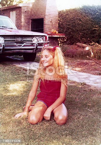Vintage grainy image from the seventies of a blonde girl sitting on the grass.